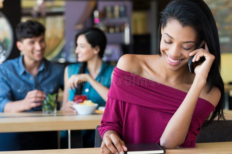 Frau, die am Handy am Café spricht lizenzfreie stockfotos