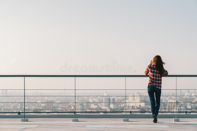 Frau, die Handy an der Dachspitze während des Sonnenuntergangs mit Kopienraum, Kommunikation oder einsamem Leutekonzept verwendet lizenzfreies stockfoto