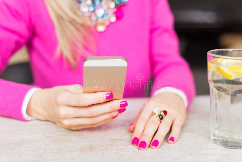 Frau, die Handy im Café verwendet lizenzfreie stockbilder
