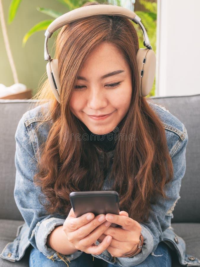 Frau, die Handy und Kopfhörer verwendet, um Musik zu hören stockbilder