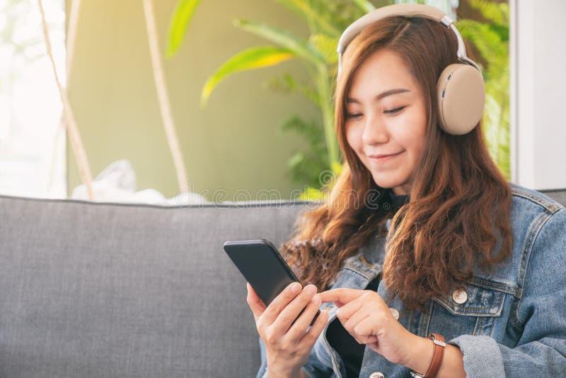 Frau, die Handy und Kopfhörer verwendet, um Musik zu hören stockfotos