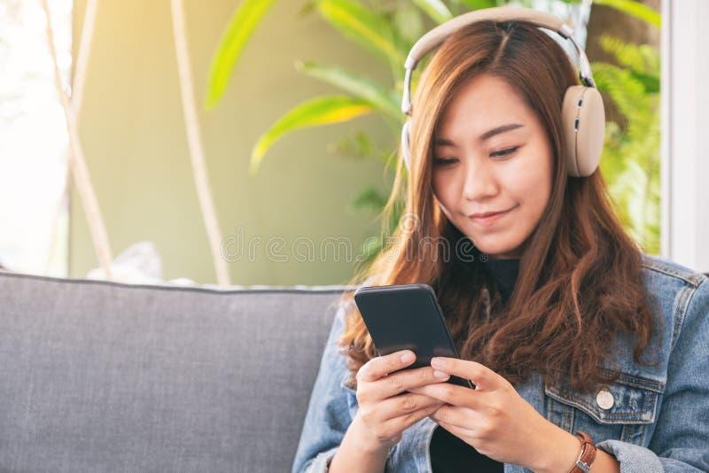 Frau, die Handy und Kopfhörer verwendet, um Musik zu hören stockbild