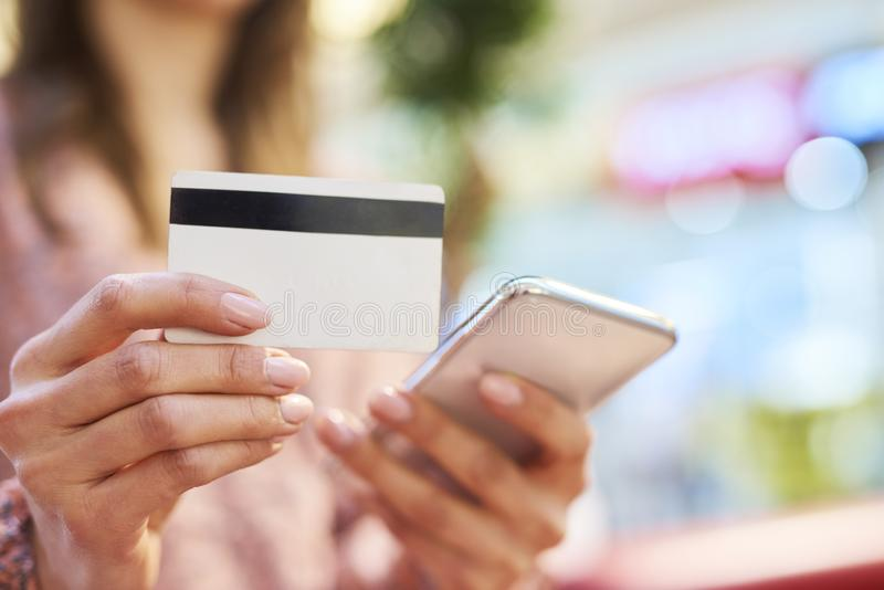 Frau, die Handy und Kreditkarte während des on-line-Einkaufens verwendet lizenzfreies stockbild