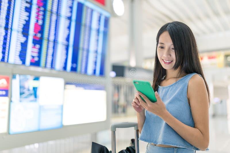 Frau, die Handy verwendet, um ihren Flugplan zu überprüfen lizenzfreie stockbilder