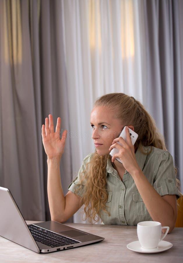 Frau, die am Handy vor Laptop spricht lizenzfreie stockfotografie