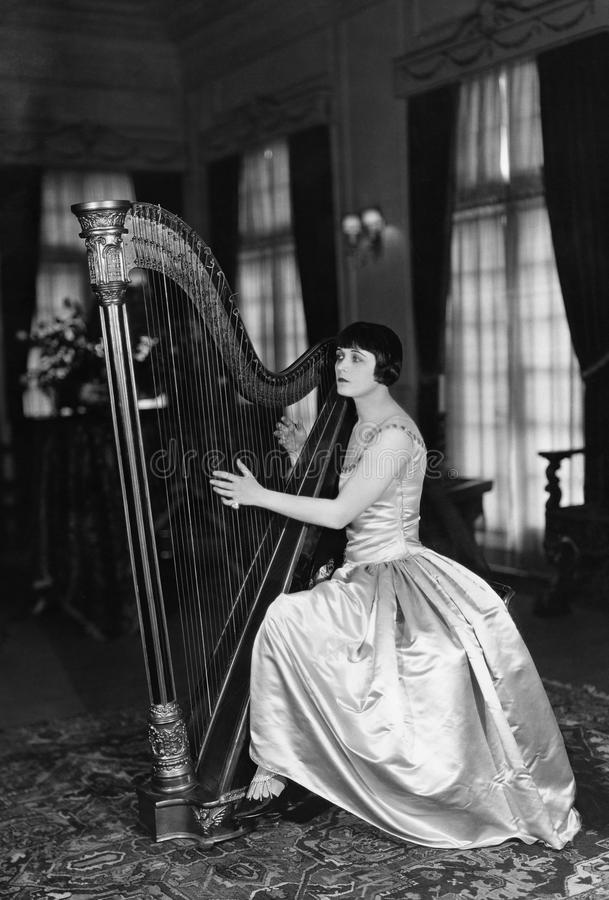 Frau, die Harfe spielt (alle dargestellten Personen sind nicht längeres lebendes und kein Zustand existiert Lieferantengarantien, stockbild