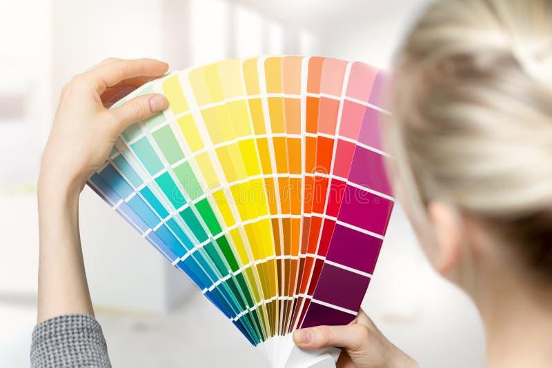Frau, die Hauptinnenfarbenfarbe vom Musterkatalog vorwählt lizenzfreie stockfotografie