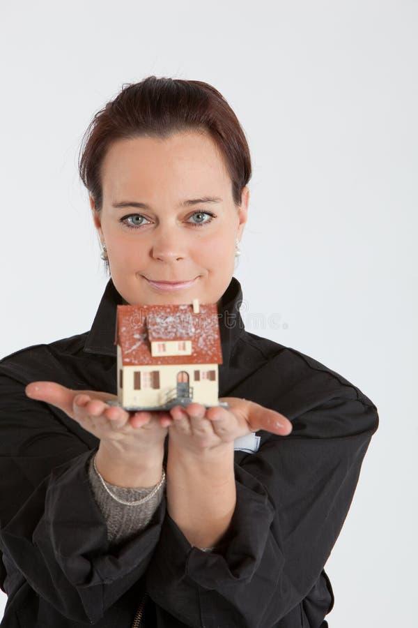 Frau, die Haus herausstellt stockfotografie