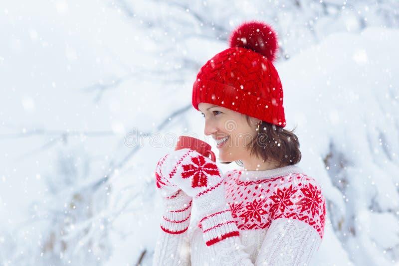 Frau, die heiße Schokolade am Weihnachtsmorgen im schneebedeckten Garten trinkt Mädchen in der gestrickter nordischen Strickjacke stockfotos
