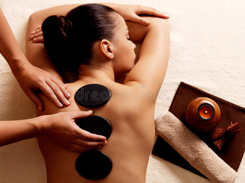 Frau, die heiße Steinmassage im Badekurortsalon erhält. stockbild
