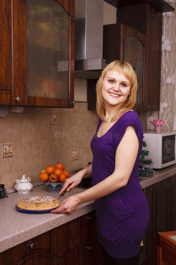 Frau, die heißen Apfelkuchen an der Küche schneidet stockbild