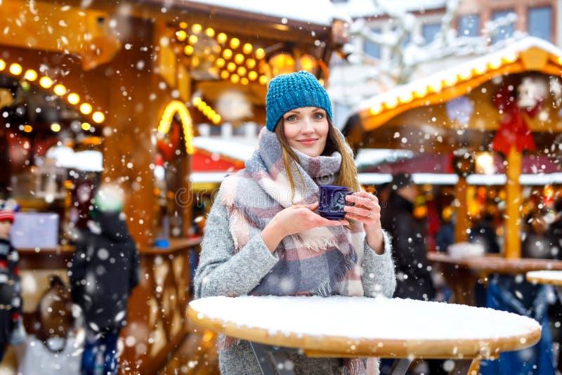 Frau, die heißen Durchschlag auf deutschem Weihnachtsmarkt trinkt stockfotos