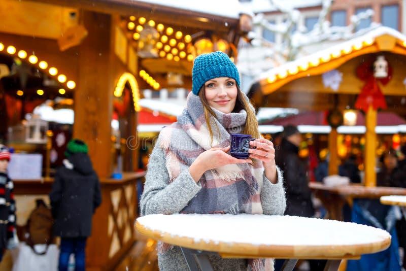 Frau, die heißen Durchschlag auf deutschem Weihnachtsmarkt trinkt stockbilder