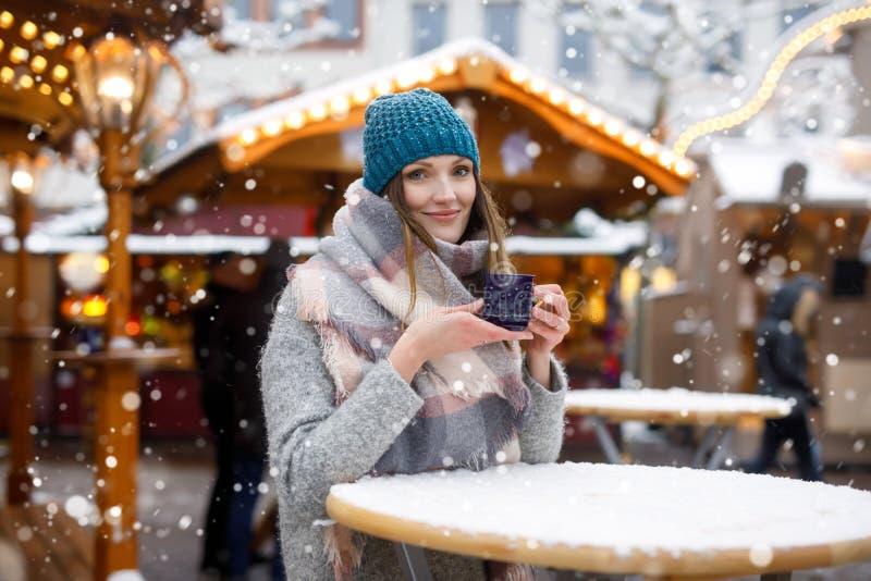 Frau, die heißen Durchschlag auf deutschem Weihnachtsmarkt trinkt stockfoto