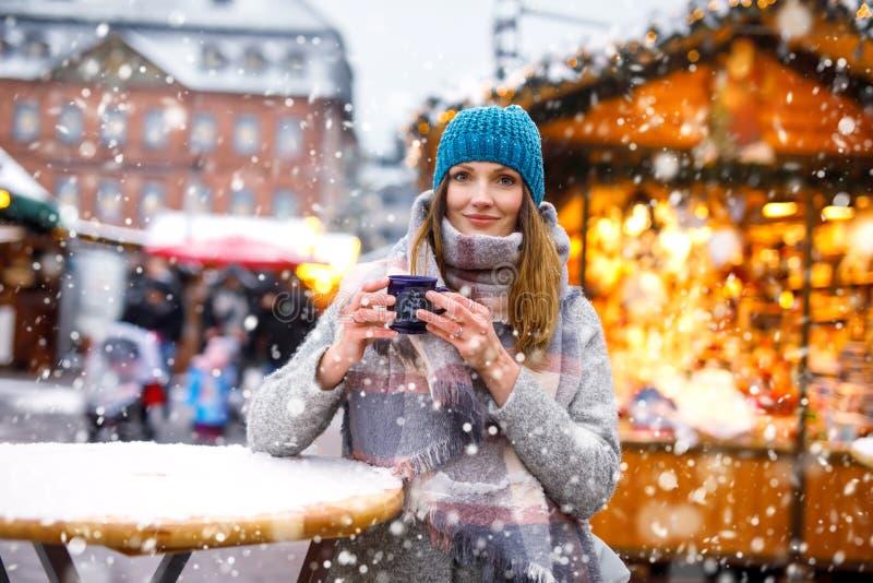Frau, die heißen Durchschlag auf deutschem Weihnachtsmarkt trinkt stockbild