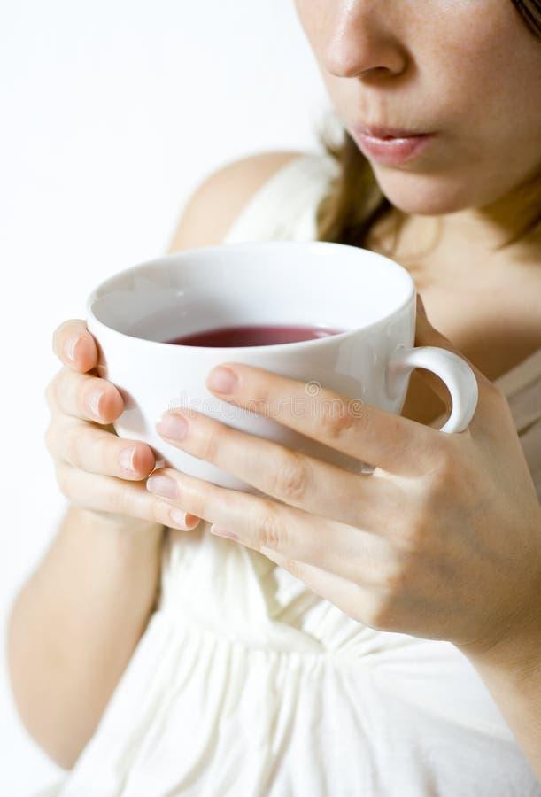 Frau, die heißes Getränk abkühlt stockbilder