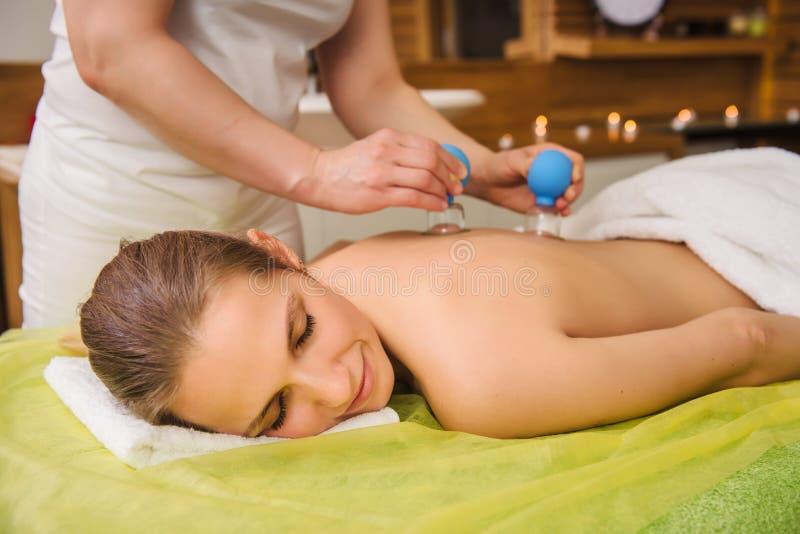 Frau, die heißes Glasvakuumhöhlende Massage in der Badekurortmitte hat lizenzfreies stockfoto