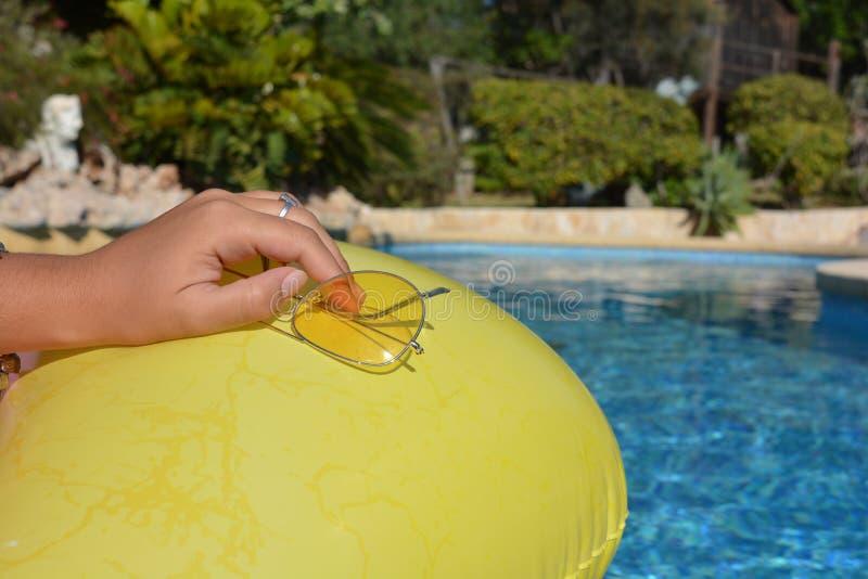 Frau, die helle gelbe Sonnenbrille hält lizenzfreies stockfoto