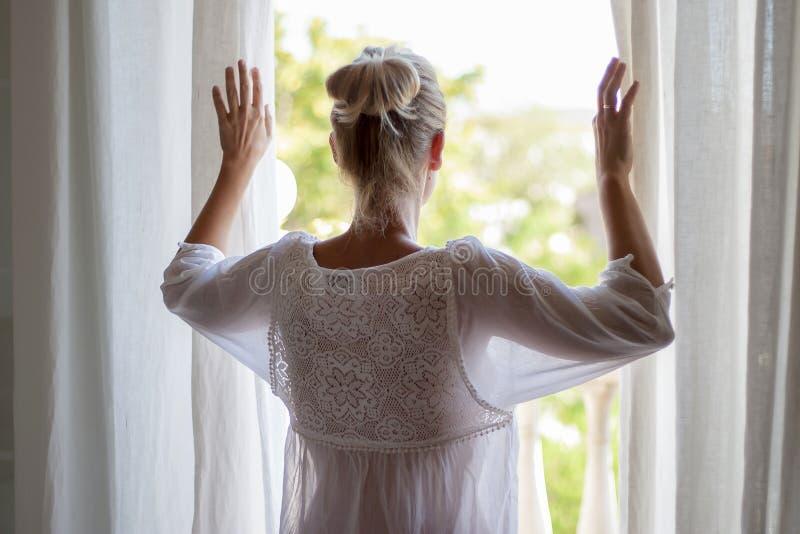 Frau, die heraus das Fenster im pijama schaut lizenzfreie stockfotos
