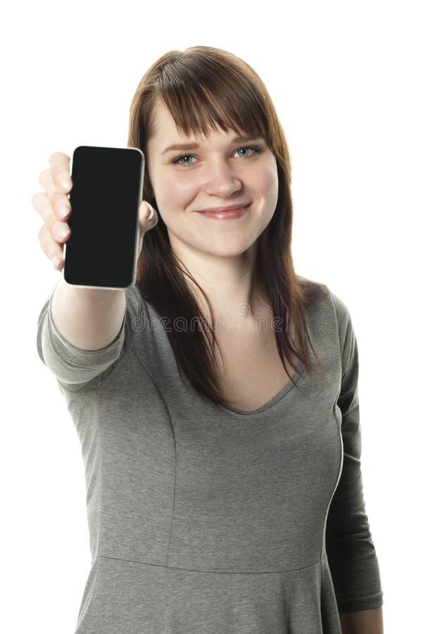 Frau, die heraus einen Handy auf weißem Hintergrund anhält lizenzfreie stockfotos
