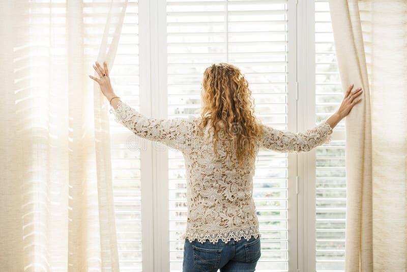 Frau, die heraus Fenster schaut lizenzfreies stockfoto