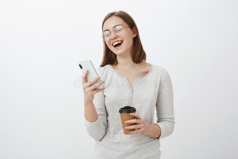 Frau, die heraus laute Lesungslustigen Witz oder meme im Internet betrachtet den Smartphoneschirm hält Papiertasse kaffee lacht lizenzfreie stockfotografie