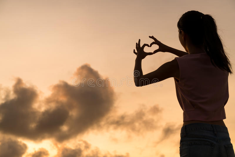 Frau, die Herzsymbol mit ihren Händen bei Sonnenuntergang macht lizenzfreies stockfoto