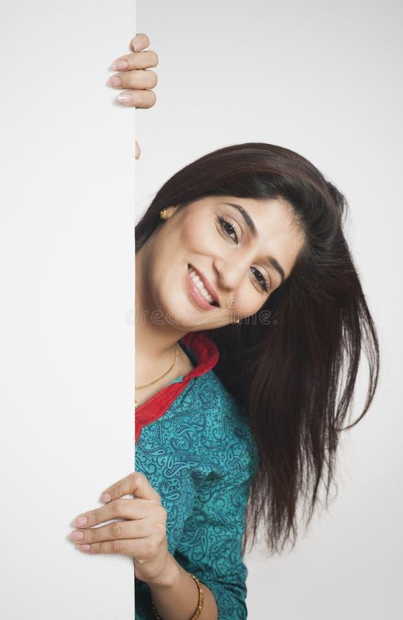 Frau, die hinten von einer Wand späht stockfotografie