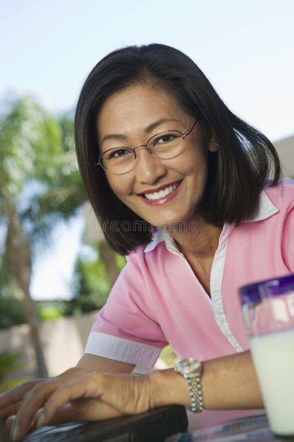 Frau, die am Hinterhoftisch unter Verwendung des Laptops sitzt lizenzfreie stockbilder
