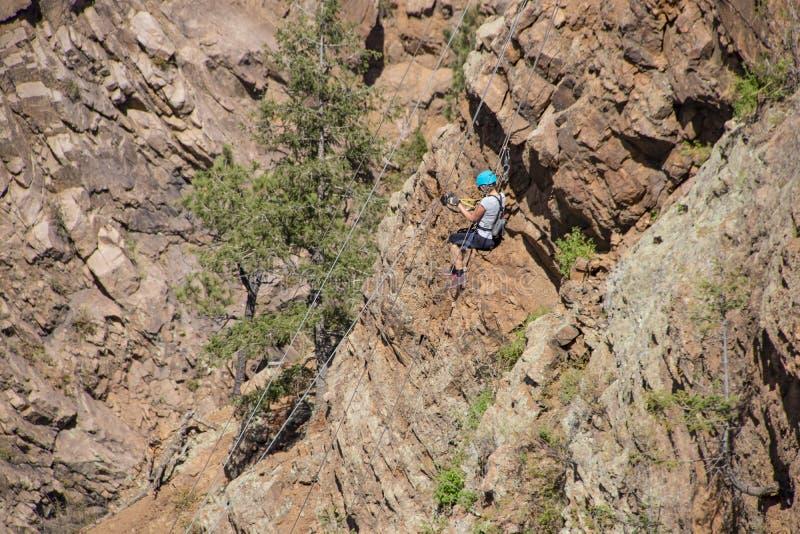 Frau, die hinunter eine Klippe in Rocky Mountains von Colorado ziplining ist stockfotografie