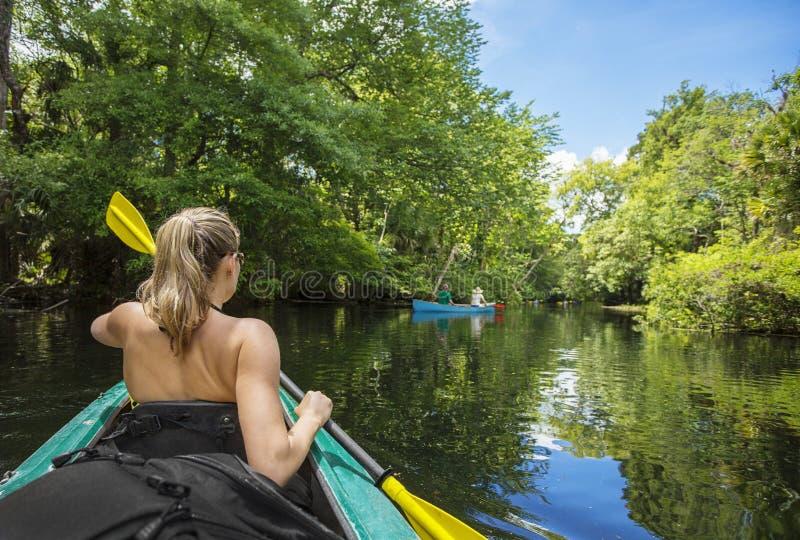 Frau, die hinunter einen schönen tropischen Dschungelfluß Kayak fährt lizenzfreie stockfotografie
