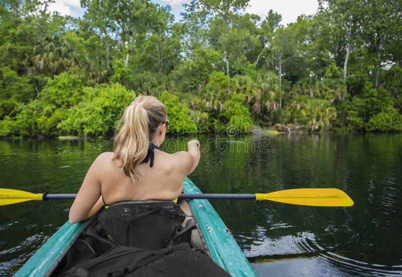 Frau, die hinunter einen schönen tropischen Dschungelfluß Kayak fährt lizenzfreies stockfoto