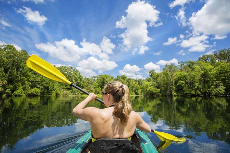 Frau, die hinunter einen schönen tropischen Dschungelfluß Kayak fährt stockfotos