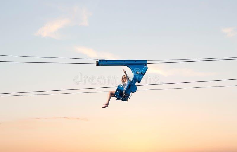 Frau, die hoch in die Luft auf eine Ziplinie fährt stockfotografie