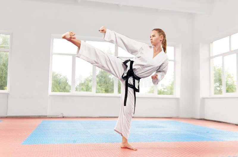 Frau, die hohen Tritt der Kampfkünste an der Kampfklasse durchführt stockfoto