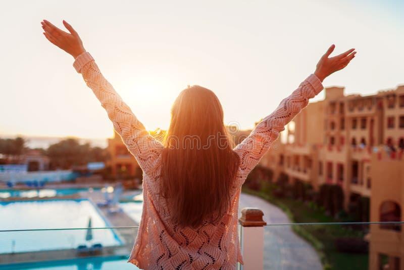 Frau, die am Hotelbalkon genießt Sonnenaufgang mit Swimmingpool- und Seeansicht sich entspannt stockfotografie