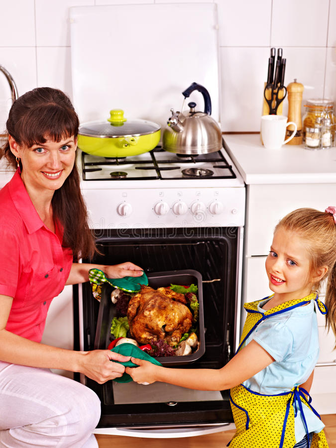 Frau, die Huhn an der Küche kocht lizenzfreie stockfotos