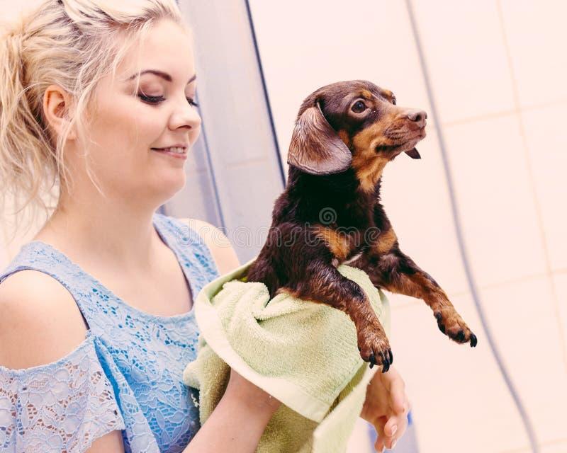 Frau, die Hund nach Bad trocknet lizenzfreies stockbild