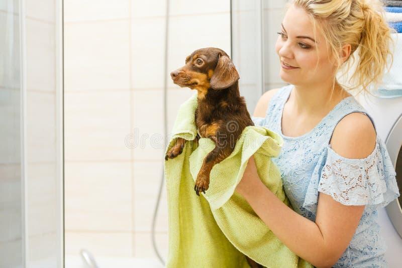 Frau, die Hund nach Bad trocknet lizenzfreie stockfotos