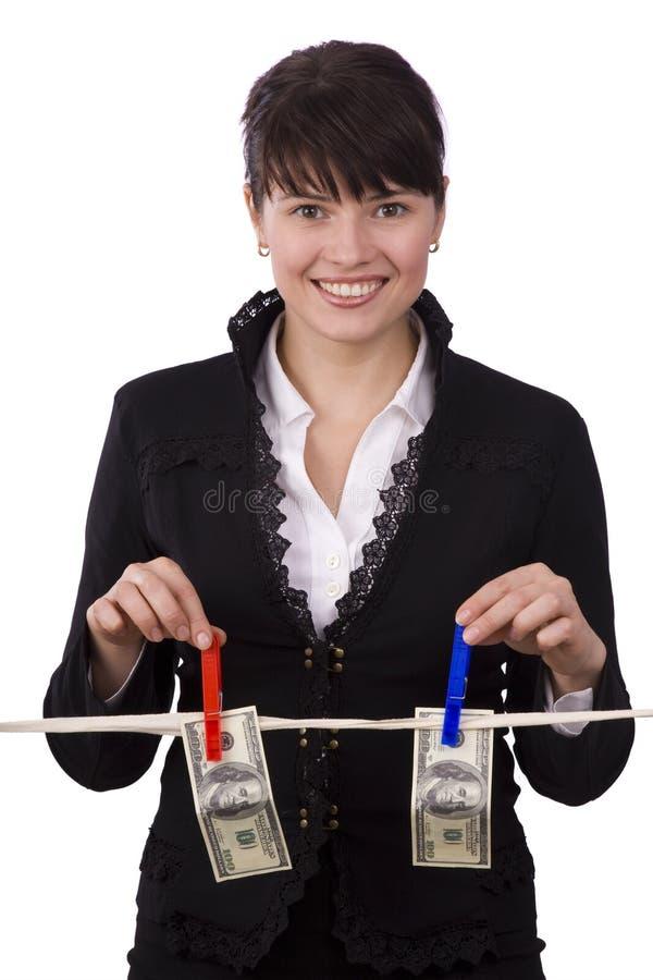 Frau, die hundert Dollarscheine auf Wäscheleine hängt stockbild