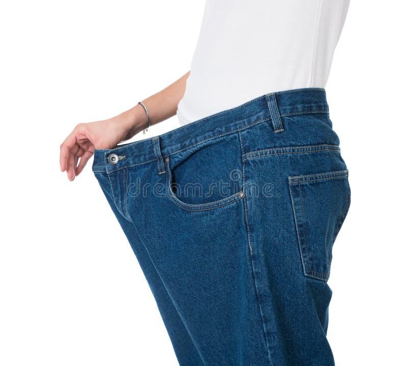 Frau, die ihr alte Jeans nach erfolgreicher Diät zeigt lizenzfreie stockfotografie