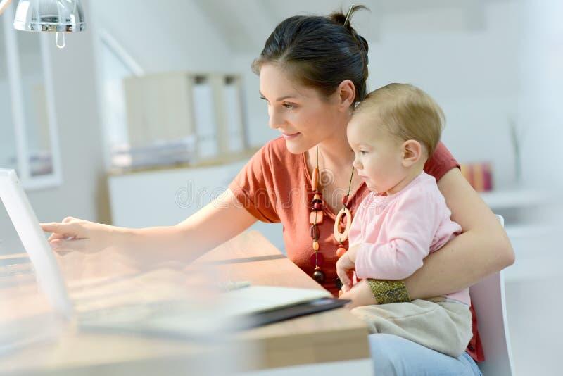 Frau, die ihr Baby hält und an Laptop arbeitet stockfoto