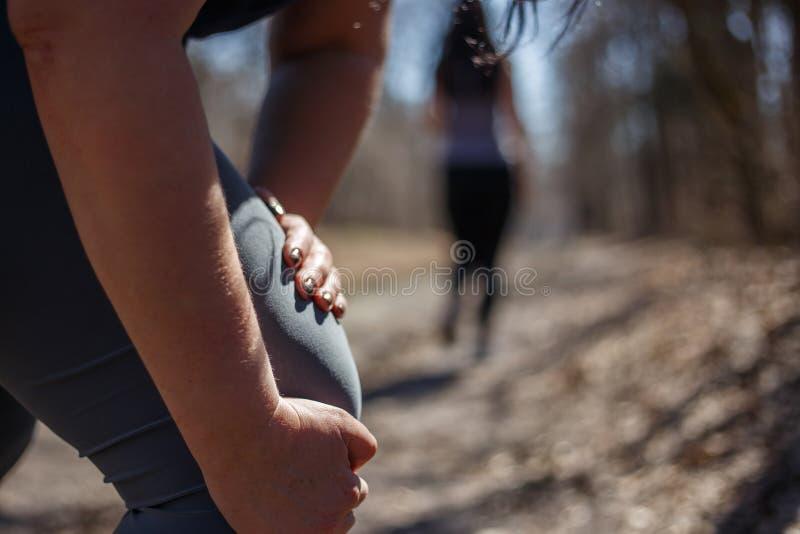 Frau, die ihr Bein, ein Knietrauma Rütteln erhalten am im Freien berührt SP stockbilder