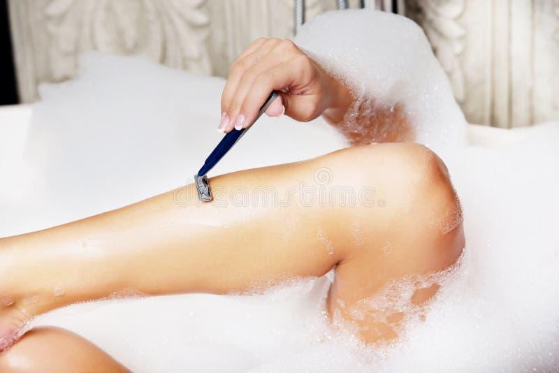Frau, die ihr Bein rasiert stockfotografie