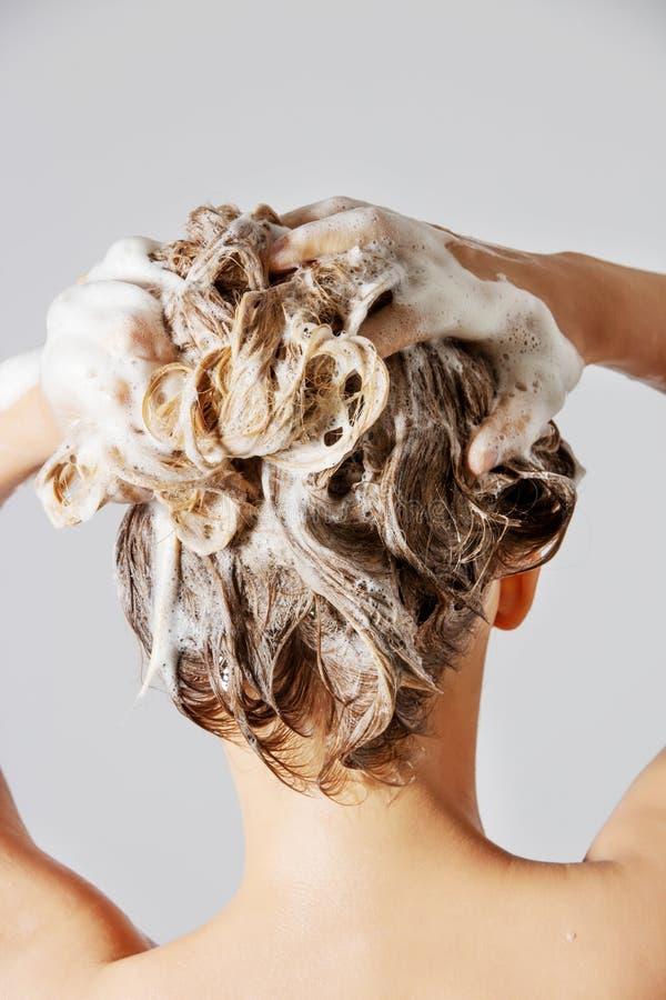 Frau, die ihr blondes Haar wäscht lizenzfreies stockfoto
