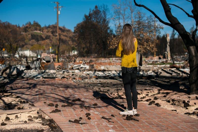 Frau, die ihr gebranntes Haus nach Feuerunfall betrachtet stockbild