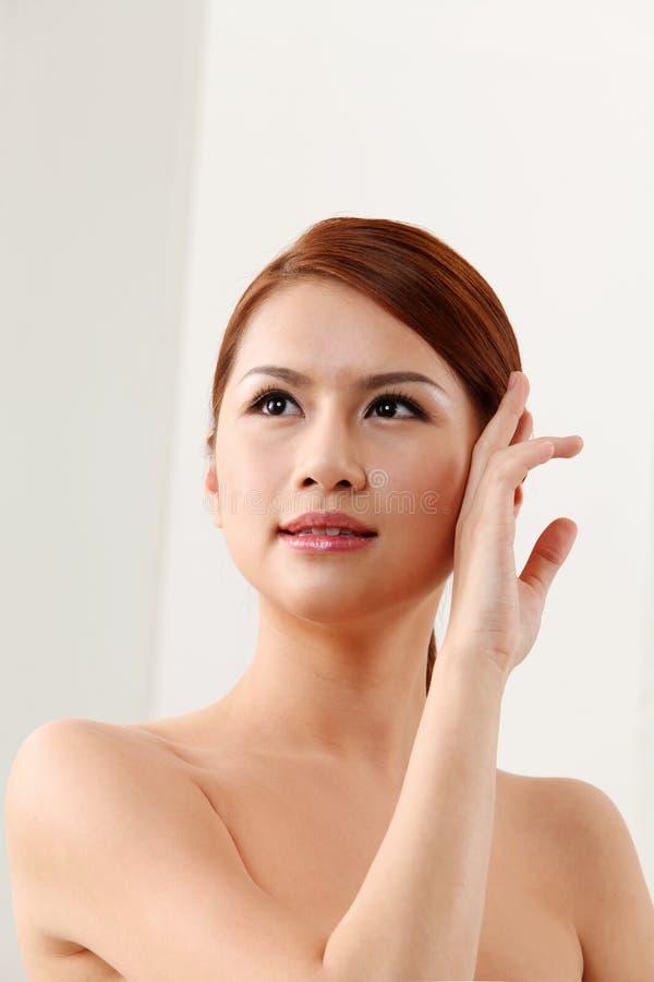 Frau, die ihr Gesicht berührt lizenzfreie stockbilder