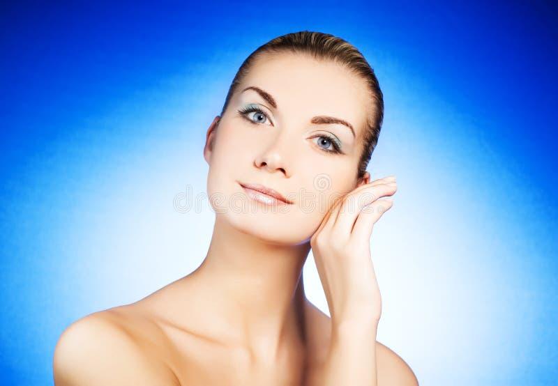 Frau, die ihr Gesicht massiert lizenzfreie stockfotos