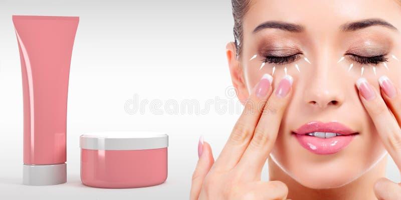 Frau, die ihr Gesicht mit den Fingern und den Kosmetik Rohr und Glas massiert lizenzfreies stockbild