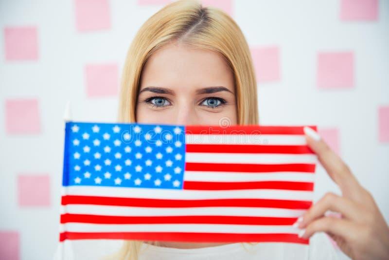 Frau, die ihr Gesicht mit USA-Flagge bedeckt lizenzfreie stockbilder